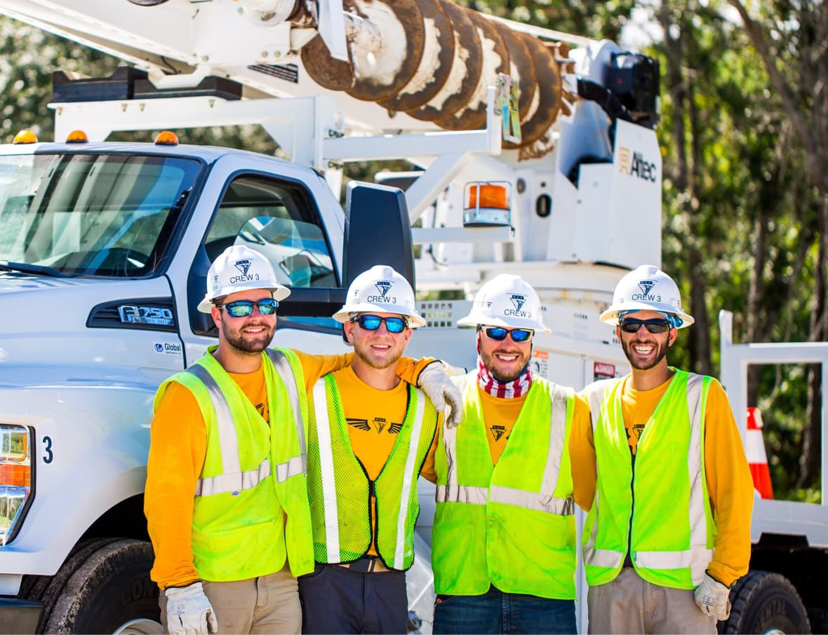 Four lineman standing beside truck